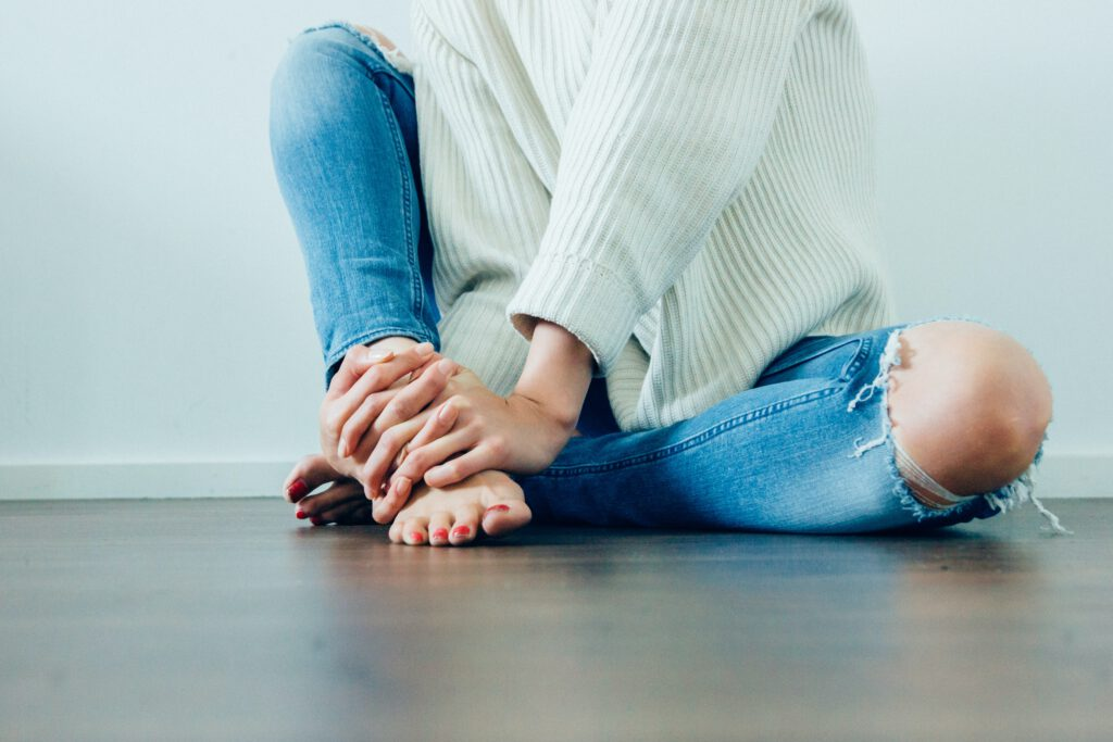 person wearing distressed blue denim jeans inside room